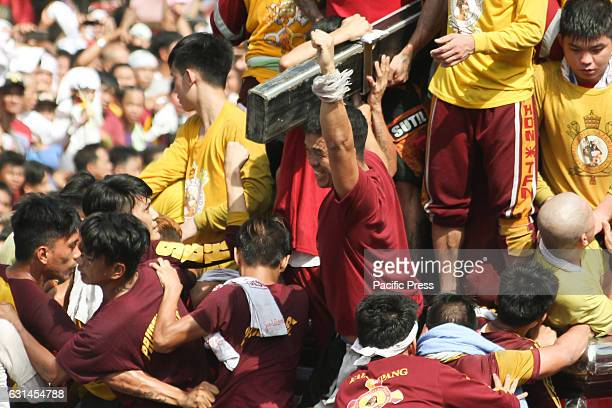 AVE MANILA NCR PHILIPPINES A devotee cheers wildly after being able to kiss the cross of the miraculous Icon of the Black Nazarene Devotees observe...