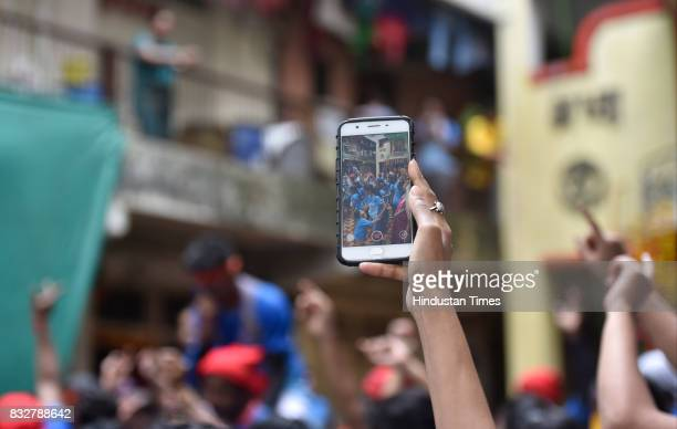 A devotee clicks picture on his mobile as Govinda revellers form human pyramid on the occasion of Gokulashtami at Prabhadevi on August 15 2017 in...