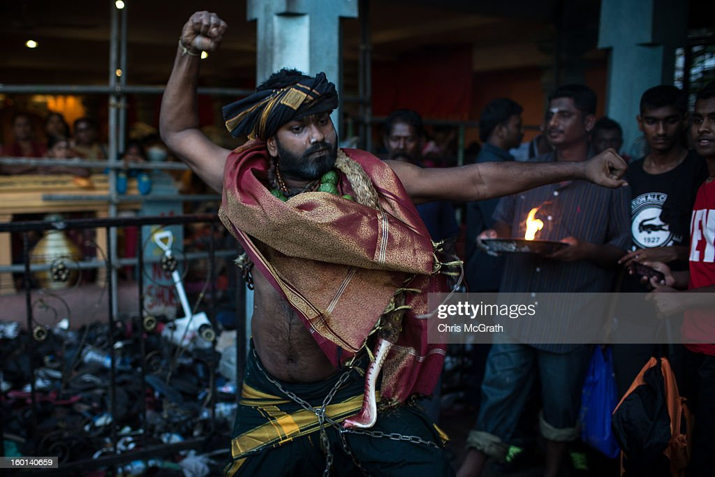 A devotee dances before walking up the 272 steps to the entrance of the Batu Caves during the Thaipusam procession on January 27, 2013 in Batu Caves, Malaysia. Thaipusam is a Hindu festival celebrated on the full moon in the Tamil month of Thai. The festival marks the birthday of Lord Muruga and also commemorates the day Hindu Goddess Parvati gave her son a lance to defeat the evil demon Soorapadamwhen. The festival sees devotees carry milk pots to seek forgivness and some will carry a 'Kavadi' many of which are attached via, strings, hooks, and skews pierced into the carriers skin.