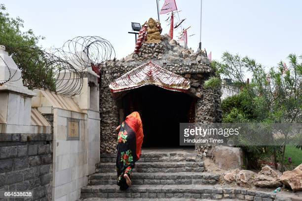 A devotee enters the cave to offer prayers on Asthami the eighth day of the festival of Navratri at Mata Mandir on April 4 2017 in New Delhi India...