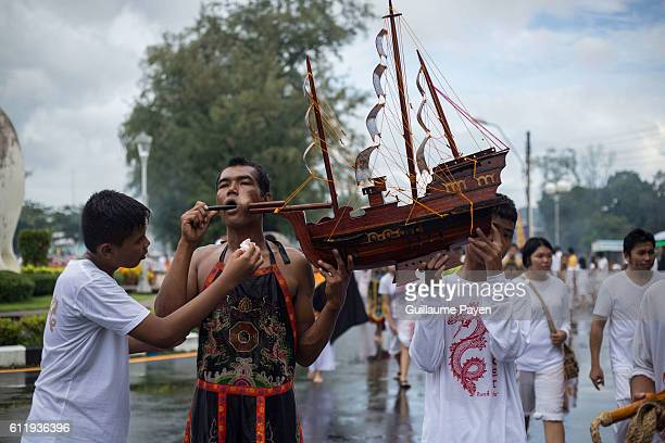 A devotee from the Chinese Choor Su Gong Naka Shrine has his cheek pierced with a model of wodden boat attends a street procession during the yearly...
