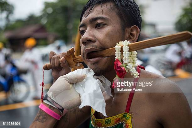 A devotee from the Chinese Choor Su Gong Naka Shrine has his cheek pierced with a wodden sword attends a street procession during the yearly...