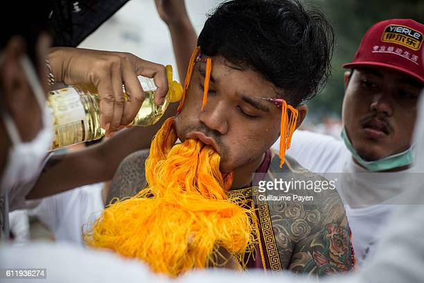 A devotee from the Chinese Choor Su Gong Naka Shrine has his cheek pierced with coloured yarn attends a street procession during the yearly...