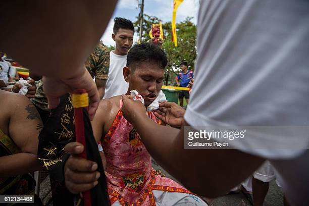 A devotee from the Chinese Kuan Tae Kun Shrine receive healthcare after being pierced with a metal ring during the yearly Vegetarian Festival also...