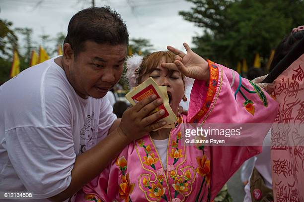 A devotee from the Chinese Kuan Tae Kun Shrine receive healthcare after being pierced with a metal spear during the yearly Vegetarian Festival also...