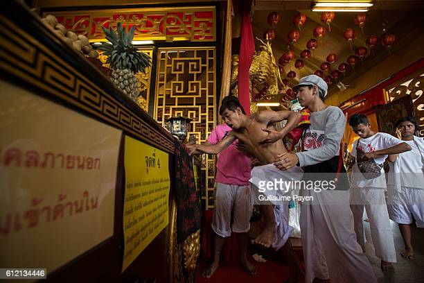 A devotee from the Chinese Kuan Tae Kun Shrine works himself out of a trance at the end of the ceremony after being possessed by the spirit of god...