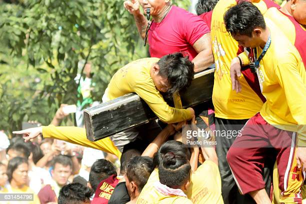 AVE MANILA NCR PHILIPPINES A devotee hangs limply across the cross of the Black Nazarene out of exhaustion after successfully touching the miraculous...