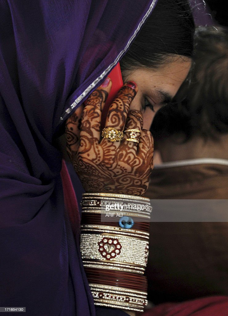A devotee, her hand adorned with henna art, talks over her mobile phone at a Sikh shrine in Lahore on June 29, 2013, on the 174th death anniversary of Maharaja Ranjit Singh. Singh was also known as 'Sher-e-Punjab' or 'Lion of Punjab' and is remembered for uniting the Punjab as a strong nation and his possession of the Koh-i-noor diamond. Singh, who was born in Gujranwala in 1780, was the ruler of the Pakistani Punjab province and died on June 27, 1839. AFP PHOTO/Arif ALI