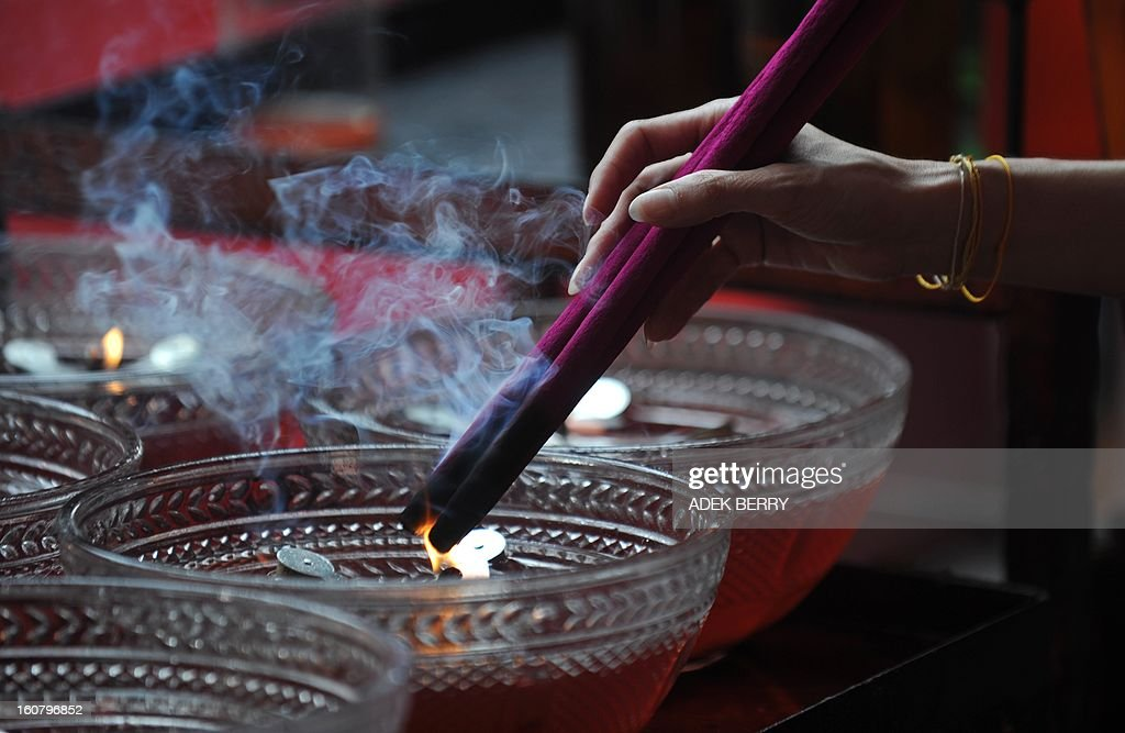 A devotee holds incense sticks as she prays at the Jin De Yuan Buddhist temple, locally known as Vihara Dharma Bhakti, ahead of the Chinese Lunar New Year, in Jakarta on February 6, 2013. The Chinese New Year of the Snake falls on February 10, 2013. AFP PHOTO / ADEK BERRY