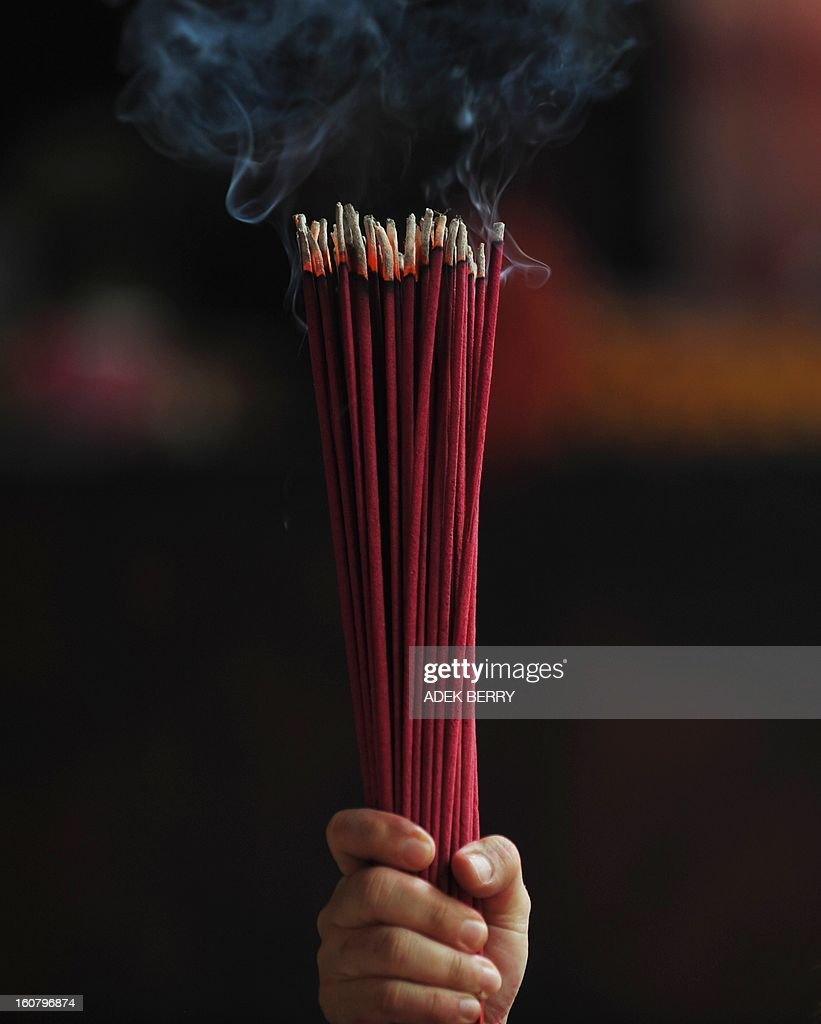 A devotee holds incense sticks as she prays at the Jin De Yuan Buddhist temple, locally known as Vihara Dharma Bhakti, ahead of the Chinese Lunar New Year, in Jakarta on February 6, 2013. The Chinese New Year of the Snake falls on February 10, 2013.