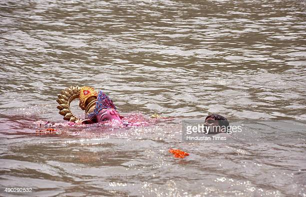 A devotee immerse a statue of the Hindu God Ganesha in Yamuna River on the last day of the Ganesh Chaturthi festival at Ghaziabad on September 27...