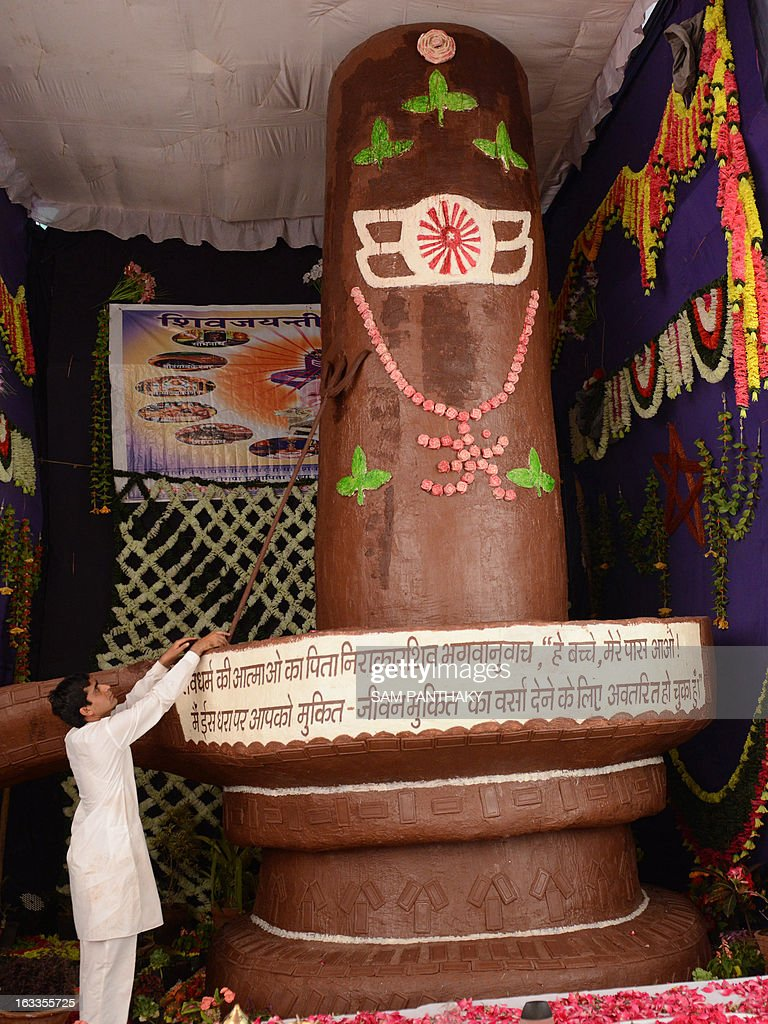 A devotee is pictured near a shivling made from chocolate in Ahmedabad on March 8, 2013, ahead of the Maha Shivratri festival. The chocolate shivling, a phallic representation of the Hindu deity Shiva, weighing some 500 kilograms and 5.36 meters tall, will be distributed to charitable homes following the conclusion of the religous festival. AFP PHOTO / Sam PANTHAKY