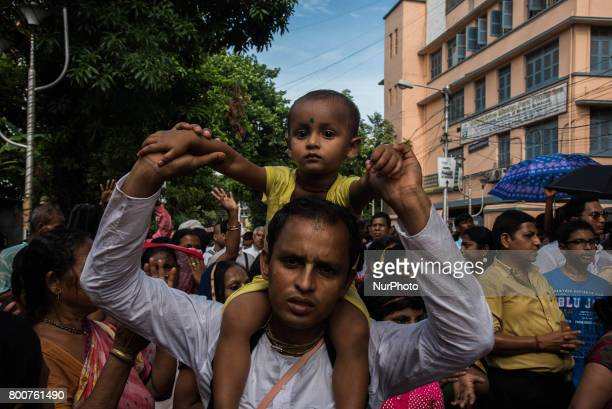 A devotee is walking in the procession with his daughter on his shoulders as she is too small to walk herself in the procession during rath yatra in...