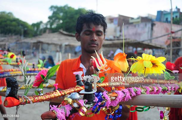 A devotee known as Kanwariya offers prayer before carried holy water from the River Ganges near the northern Indian city of Allahabad Kanwarias are...