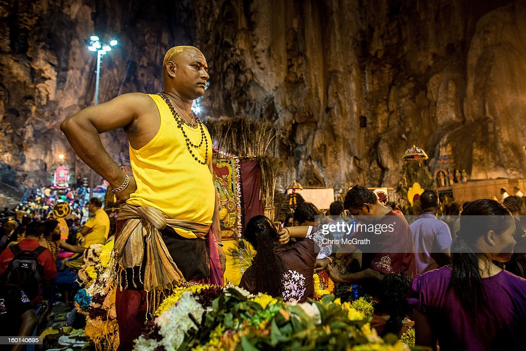 A devotee looks out over the crowd inside the Batu Caves during the Thaipusam procession on January 27, 2013 in Batu Caves, Malaysia. Thaipusam is a Hindu festival celebrated on the full moon in the Tamil month of Thai. The festival marks the birthday of Lord Muruga and also commemorates the day Hindu Goddess Parvati gave her son a lance to defeat the evil demon Soorapadamwhen. The festival sees devotees carry milk pots to seek forgivness and some will carry a 'Kavadi' many of which are attached via, strings, hooks, and skews pierced into the carriers skin.