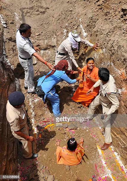 A devotee of Indian Hindu Akhara leader Trikal Bhawanta grapples with police officials as she undergoes a burial ritual in Ujjain on April 26 during...
