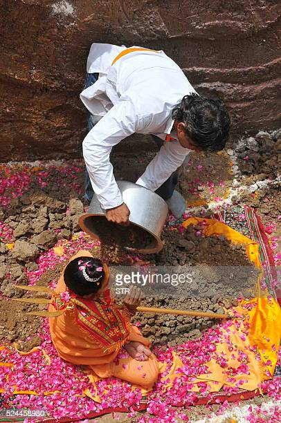 A devotee of Indian Hindu Akhara leader Trikal Bhawanta uses a bowl to cover her with mud as she undergoes a burial ritual in Ujjain on April 26...