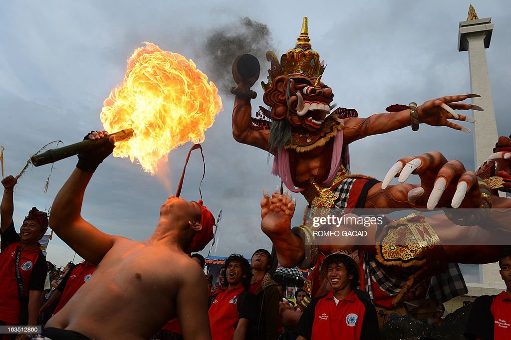 A devotee of Indonesia's minority Hindu blows flames during a parade of 'Ogoh Ogoh' effigies at Jakarta's central National Monument on March 11, 2013 on the eve of Nyepi or Day of Silence. The effigies symbolizes evil and after the procession are torched in a symbolic act of destroying all the negative and demonic elements in the universe and will usher in Hindu's total Day of Silence on March 12, 2013. AFP PHOTO / ROMEO GACAD