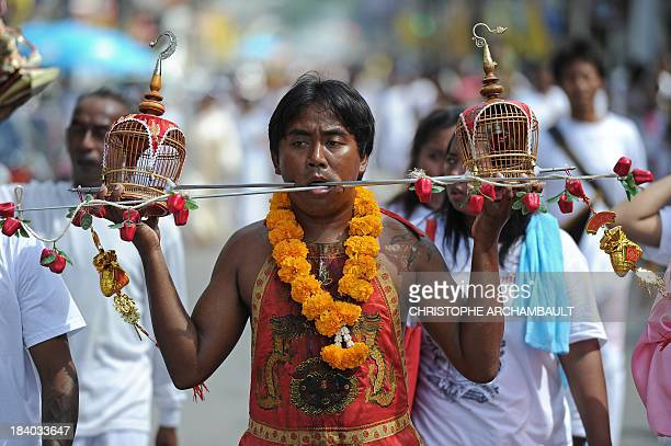 A devotee of the Chinese Jui Tui Shrine holds bird cages attached to metal rods during a street procession as part of the annual Vegetarian Festival...
