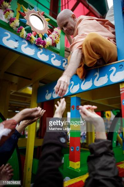 A devotee of the Hare Krishna faith distributes food gifts from a Chariot during the festival of Rathayatra on June 12 2011 in London England...