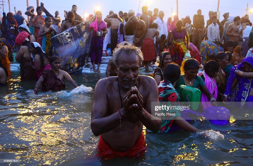 Devotee offer prayer after holydip at Sangam, the confluence of River Ganga Yamuna and mythological Saraswati on the occasion of Maghi Purnima the main holy bathing day during Magh mela festival.