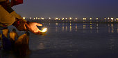 A devotee offering a lamp in river water at the bank of Sangam on the auspicious occasion of Paush Purnima on January 5 2015 in Allahabad India Magh...