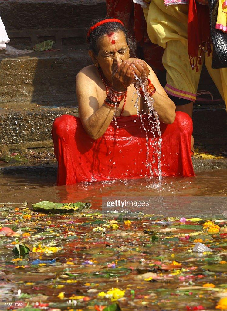 MATATIRTHA, KATHMANDU, NEPAL - : A devotee offers prayer and takes holy bath at a pond on Mata Tirtha Aunsi, or the Mother's Day.
