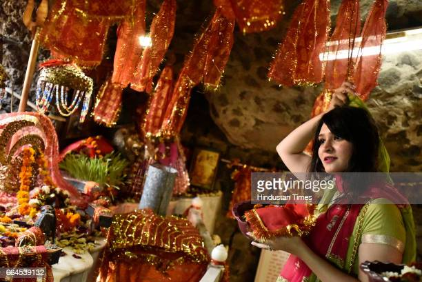 A devotee offers prayers inside a cave on Asthami the eighth day of the festival of Navratri at Mata Mandir on April 4 2017 in New Delhi India...