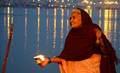 A devotee perform evening ritual at sangam during one month long Magh mela festival