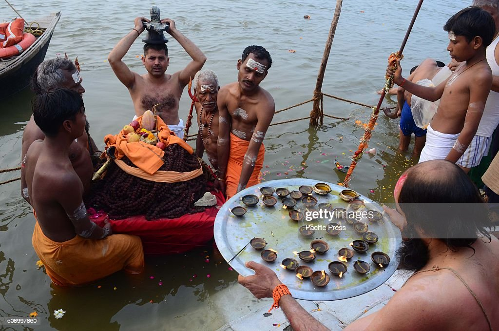 Devotee performing prayer while taking holydip at Sangam, the confluence of River Ganga Yamuna and mythological Saraswati on the occasion of Maghi Purnima the main holy bathing day during Magh mela festival.
