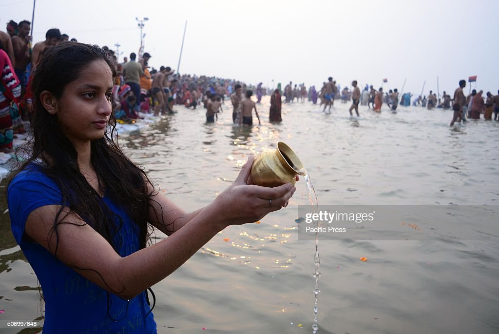 A devotee performing ritual while taking holydip at Sangam, the confluence of River Ganga Yamuna and mythological Saraswati on the occasion of Maghi Purnima the main holy bathing day during Magh mela festival.