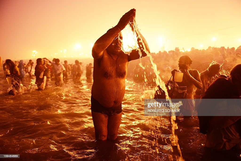 A devotee performs rituals while praying in the waters of the Sangham or the confluence of the the Yamuna and Ganges rivers during the Kumbh Mela in Allahabad on January 14, 2013. Hundreds of thousands of Hindu pilgrims led by naked, ash-covered holy men streamed into the sacred river Ganges on Monday at the start of the world's biggest religious festival. The Kumbh Mela in the Indian town of Allahabad will see up to 100 million worshippers gather over the next 55 days to take a ritual bath in the holy waters, believed to cleanse sins and bestow blessings. Before daybreak on Monday, a day chosen by astrologers as auspicious, hundreds of gurus, some brandishing swords and tridents, ran into the swirling and freezing waters for the first bath, signalling the start of events.