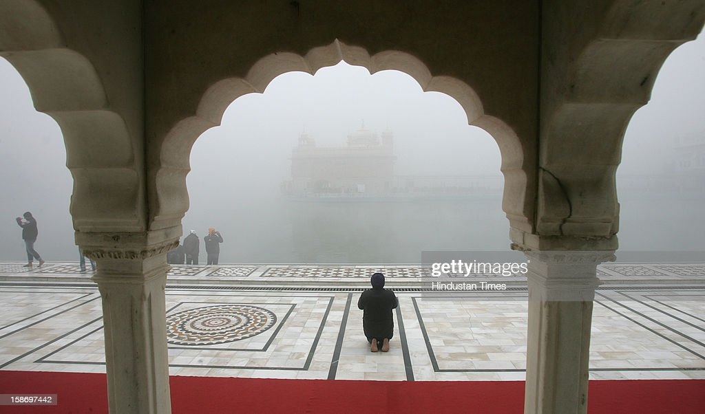 A devotee praying as fog enveloped Sanctum of Harmandar Sahib (Golden Temple) Complex on December 24, 2012 in Amritsar, India. Heavy fog in the region causes several flights and trains delayed.