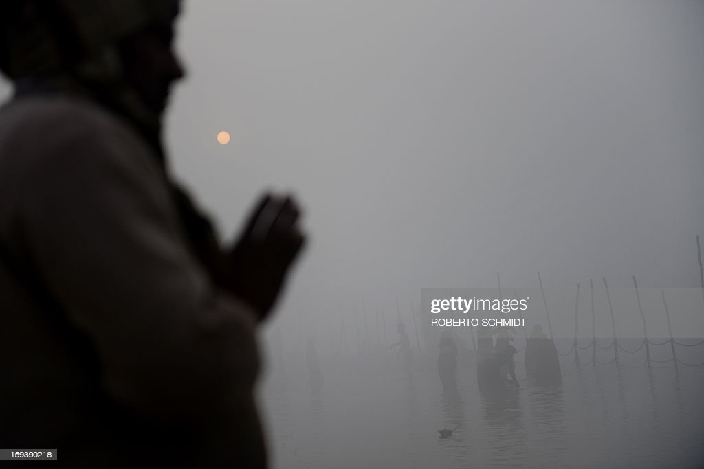A Devotee prays while others take a dip at the Sangham or confluence of the Yamuna and Ganges river at day break at the Kumbh Mela celebration in Allahabad on January 13, 2013. The Kumbh Mela in northern India, starting January 13 and stretching over 55 days, attracts ash-covered holy men who run into the frigid waters, a smattering of international celebrities, as well as millions upon millions of ordinary Indians to Allahabad, at the confluence of the rivers Yamuna and Ganges.