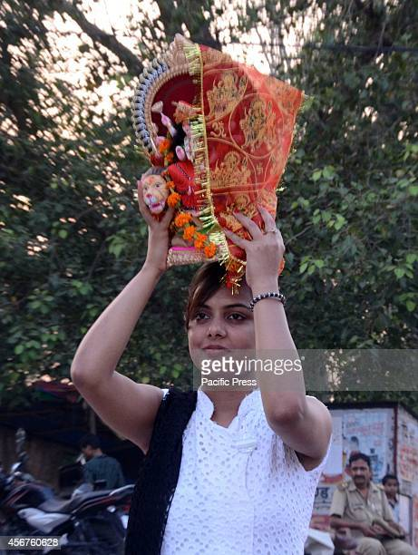 A devotee prepares to immerse an idol of the Goddess Durga into the Sangam river after the Durga Puja festival in Allahabad even the Supreme Court...