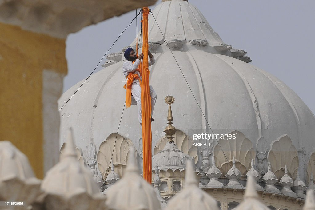 A devotee secures a cloth over a pole at a Sikh shrine in Lahore on June 29, 2013, on the 174th death anniversary of Maharaja Ranjit Singh. Singh was also known as 'Sher-e-Punjab' or 'Lion of Punjab' and is remembered for uniting the Punjab as a strong nation and his possession of the Koh-i-noor diamond. Singh, who was born in Gujranwala in 1780, was the ruler of the Pakistani Punjab province and died on June 27, 1839. AFP PHOTO/Arif ALI