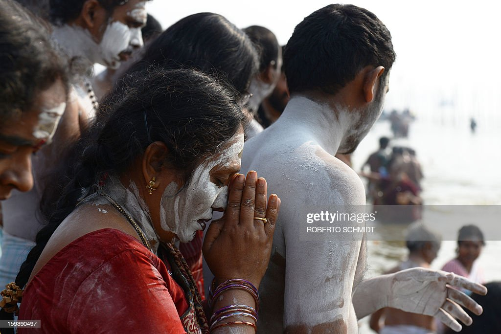 A Devotee smeared with ash prays at the waters edge before taking a dip at the Sangham or confluence of the Yamuna and Ganges river at day break at the Kumbh Mela celebration in Allahabad on January 13, 2013. The Kumbh Mela in northern India, starting January 13 and stretching over 55 days, attracts ash-covered holy men who run into the frigid waters, a smattering of international celebrities, as well as millions upon millions of ordinary Indians to Allahabad, at the confluence of the rivers Yamuna and Ganges.