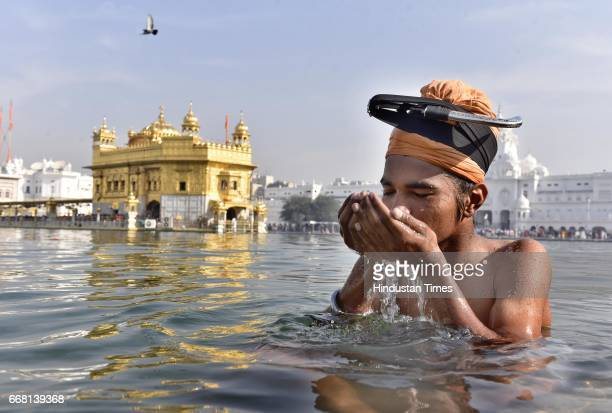 A devotee takes a holy dip at Golden Temple on the occasion of Baisakhi festival on April 13 2017 in Amritsar India Baisakhi is a historical and...