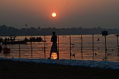 A devotee walks during sunset at sangam during one month long Magh mela festival