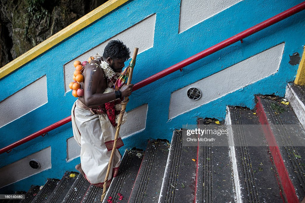 A devotee walks up the 272 steps to the entrance of the Batu Caves during the Thaipusam procession on January 27, 2013 in Batu Caves, Malaysia. Thaipusam is a Hindu festival celebrated on the full moon in the Tamil month of Thai. The festival marks the birthday of Lord Muruga and also commemorates the day Hindu Goddess Parvati gave her son a lance to defeat the evil demon Soorapadamwhen. The festival sees devotees carry milk pots to seek forgivness and some will carry a 'Kavadi' many of which are attached via, strings, hooks, and skews pierced into the carriers skin.