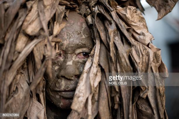 A devotee wearing a costume made of banana leaves heads to church to attend mass as part of a religious festival in honor of St John the Baptist also...