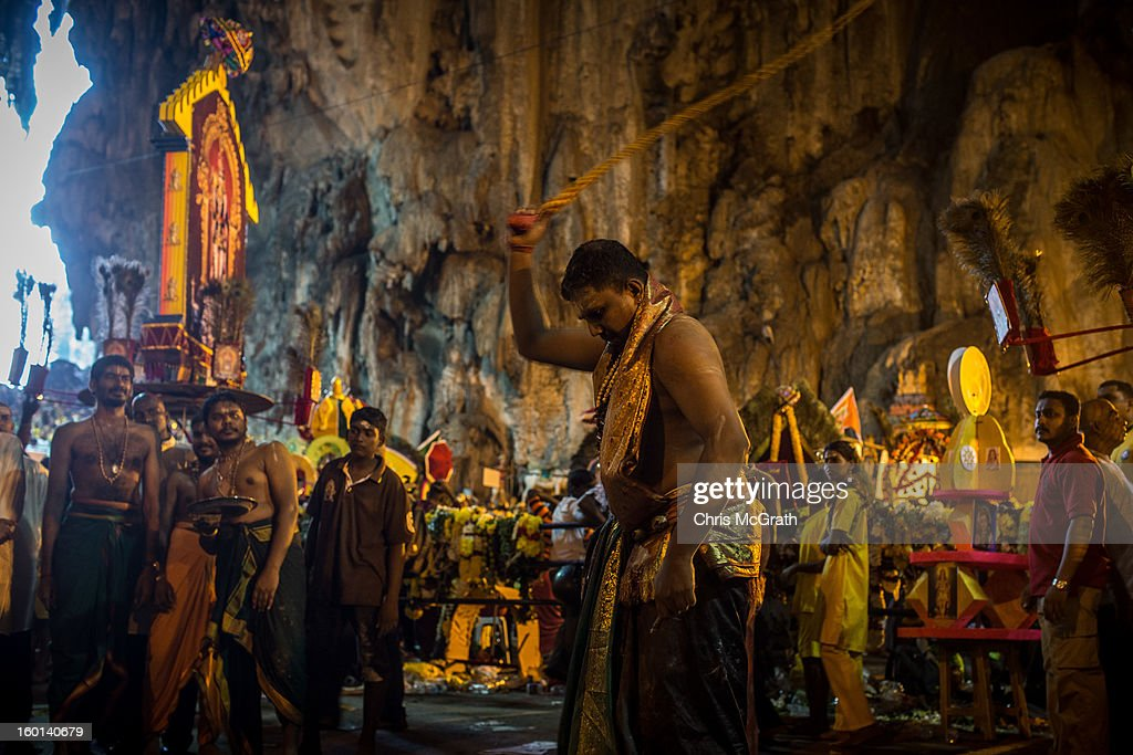 A devotee whips himself with a rope inside the Batu Caves during the Thaipusam procession on January 27, 2013 in Batu Caves, Malaysia. Thaipusam is a Hindu festival celebrated on the full moon in the Tamil month of Thai. The festival marks the birthday of Lord Muruga and also commemorates the day Hindu Goddess Parvati gave her son a lance to defeat the evil demon Soorapadamwhen. The festival sees devotees carry milk pots to seek forgivness and some will carry a 'Kavadi' many of which are attached via, strings, hooks, and skews pierced into the carriers skin.