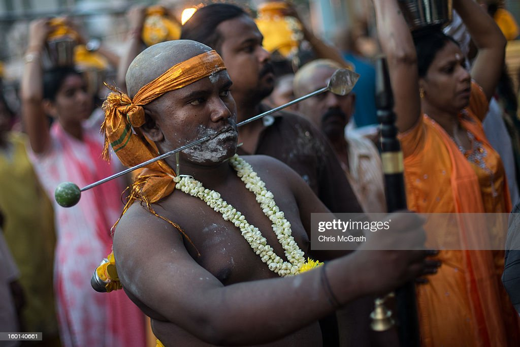 A devotee with a pierced mouth waits at the entrance to the batu Caves during the Thaipusam procession on January 27, 2013 in Batu Caves, Malaysia. Thaipusam is a Hindu festival celebrated on the full moon in the Tamil month of Thai. The festival marks the birthday of Lord Muruga and also commemorates the day Hindu Goddess Parvati gave her son a lance to defeat the evil demon Soorapadamwhen. The festival sees devotees carry milk pots to seek forgivness and some will carry a 'Kavadi' many of which are attached via, strings, hooks, and skews pierced into the carriers skin.