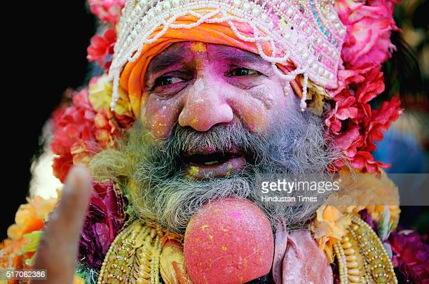 A devotee with face smeared in colors as he chants religious slogans during Holi celebrations at Banke Bihari temple on March 22 2016 in Vrindavan...