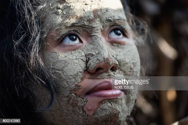 TOPSHOT A devotee with her face covered with mud and wearing a costume made of banana leaves attends a mass as part of a religious festival in honor...