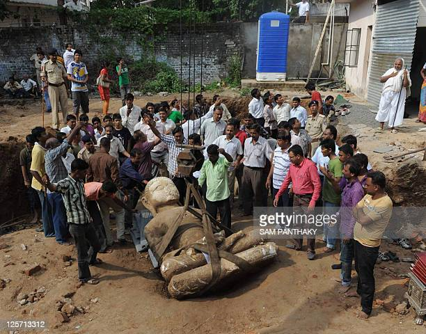 Devotees and volunteers from the Jain community work at the site where three statues of Jain Tirthankaras were recovered from a construction site of...