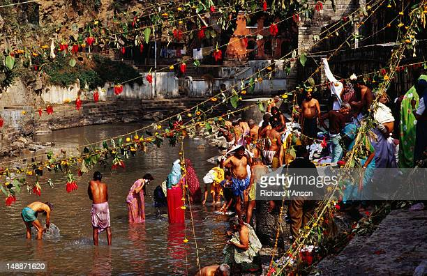 Devotees bathing in Bagmati River during Bala Chaturdashi festival at Pashupatinath Temple.