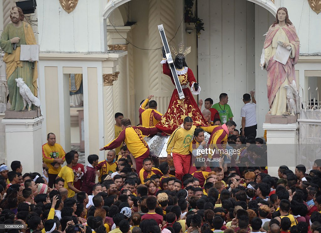 Devotees carry a replica of the Black Nazarene out of the Quiapo district church during a procession in Manila on January 7, 2016, ahead of the annual religious procession on January 9. Hundreds of thousands of barefoot devotees will on January 9 attend the annual religious procession in one of the world's biggest Catholic parades honoring an ebony statue of Jesus Christ they believe has miraculous powers. AFP PHOTO / TED ALJIBE / AFP / TED ALJIBE