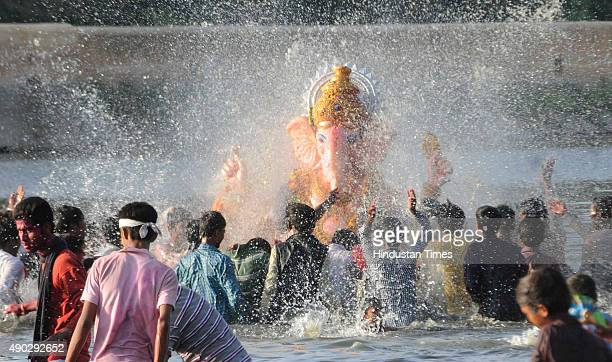 Devotees carry a statue of the Hindu God Ganesha to immerse in Amber Maotha on the last day of the Ganesh Chaturthi festival on September 27 2015 in...