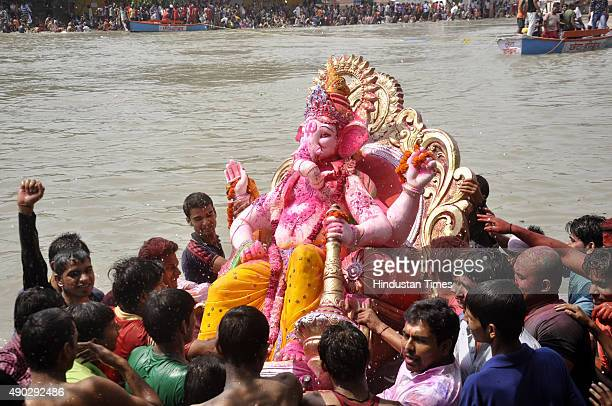 Devotees carry a statue of the Hindu God Ganesha to immerse in Yamuna River on the last day of the Ganesh Chaturthi festival at Ghaziabad on...